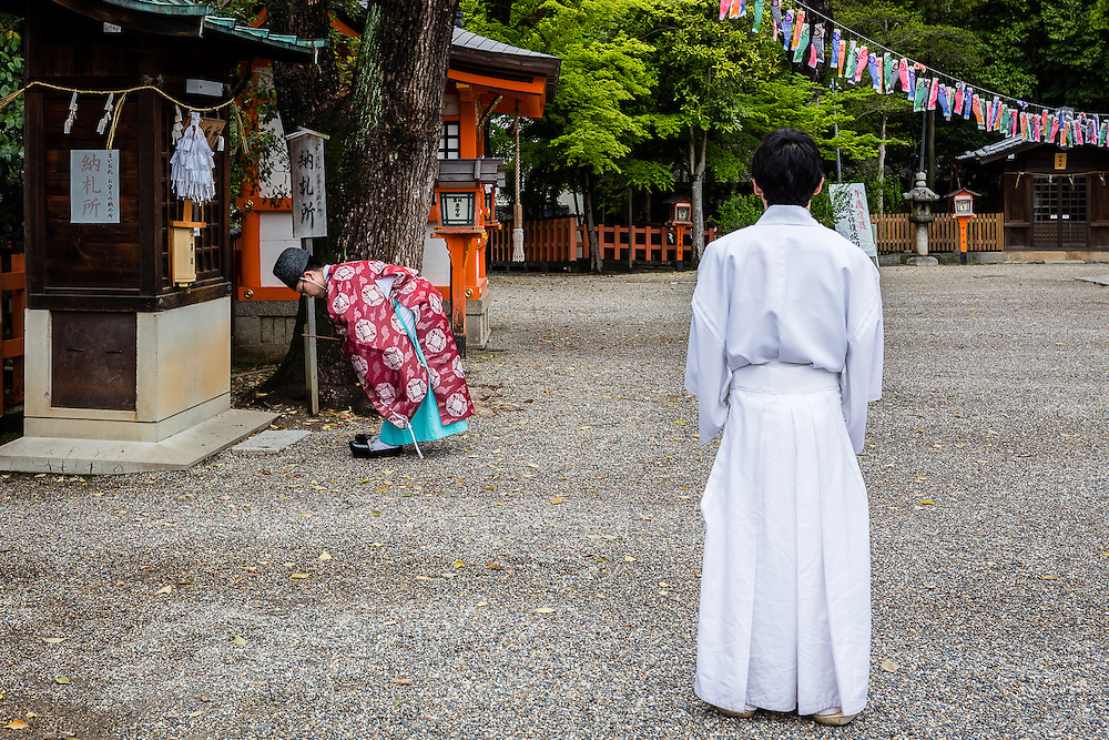 A shinto priest bows to one of the many altars in Yasaka Shrine for the morning ceremonies.