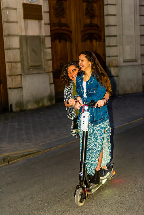 Teenaged French girls riding an electric scooter on Rue St. Dominique, Paris, France.