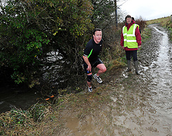 © Licensed to London News Pictures. 27/12/2012. Chadlington, Oxfordshire. The Great Brook Run. PM David Cameron took part in the run braving the very muddy conditions and swollen cold water of the Chadlington Brook Run.  Photo credit : MarkHemsworth/LNP