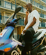 Teenage boy laughing, sitting on his scooter outside a housing estate