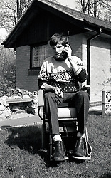 Wheelchair user with early mobile phone, UK 1990