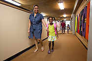 Tracy Julius (from left) and her daughter Torian Julius, 7, 1st grade, both of Cedar Rapids, walk down the hallway on the first day of school at Polk Elementary School, 1500 B Avenue NE, in Cedar Rapids on Thursday morning, July 21, 2011.
