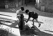 Two boys cooling off at a pump in the summer sun in Uzès, a historic town in the Gard department in the south of France.