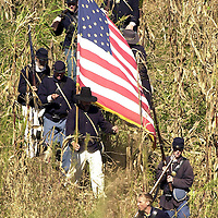 Union soldiers retreating from a strong Confederate advance carry the  American Flag through a cornfield during a reenactment of Maney's Attack,  during the weekend-long Battle of Perryville, a national Civil War Reenactment, in Perryville, Ky., on 10/5/02. Maney's Attack represents the attack of Geneeral George Maney's Confederate Brigade against Terrill's and  Starkweather's Union Brigades through a cornfield, considered to be one of  the heaviest fights in the battle.