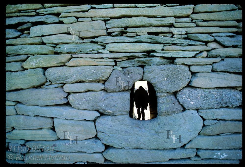 Silhouetted man enters Gallarus Oratory, as seen from outside rear window; Dingle Peninsula. Ireland