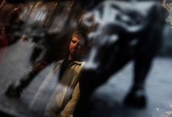 A man is reflected in a picture of a bull along Wall Street in New York, New York, USA, 21 October 2008. As Wall Street descend into a financial turmoil not seen since the stock market crash of 1929 and financial businesses were pommeled into rampant sell-offs in stocks and face regulatory changes to their business practices, professionals and non-professionals working in the district's banks, stock-trading houses and insurance companies are showing stress and a gloom not unlike the times of the Great Depression.