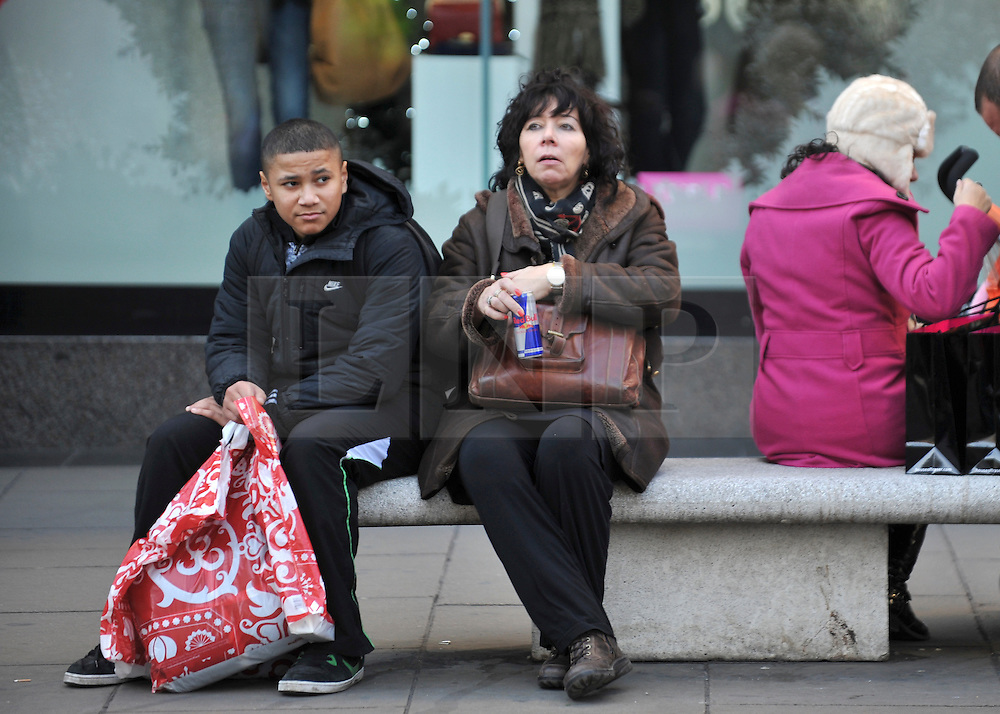 © Licensed to London News Pictures. 09/12/2011, London, UK. A young boy and a woman take a break on a bench in Oxford Street. Christmas shoppers in London's Oxford Street and Regent Street today 09 December 2011. Some of the shops are already having sales and displaying prices in windows. Photo credit : Stephen Simpson/LNP