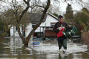 Milk man delivers milk to flooded homes on Friary Island, Wraysbury near Staines. Flood waters remain high after last weeks flooding across the Thames valley. UK<br /><br />Picture by Zute Lightfoot