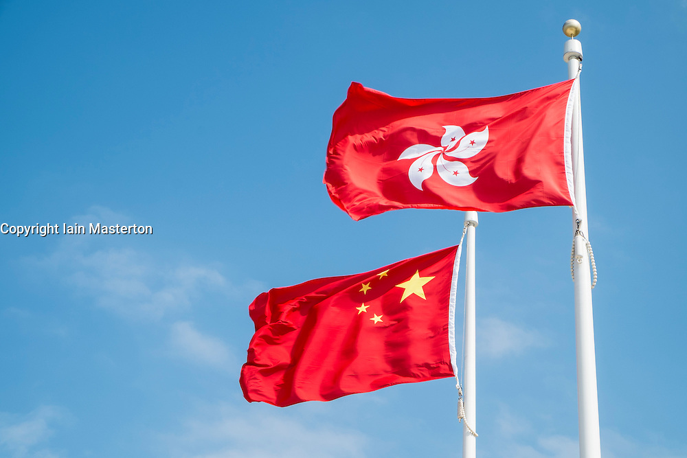Flags of China and Hong Kong flying on flagpoles.