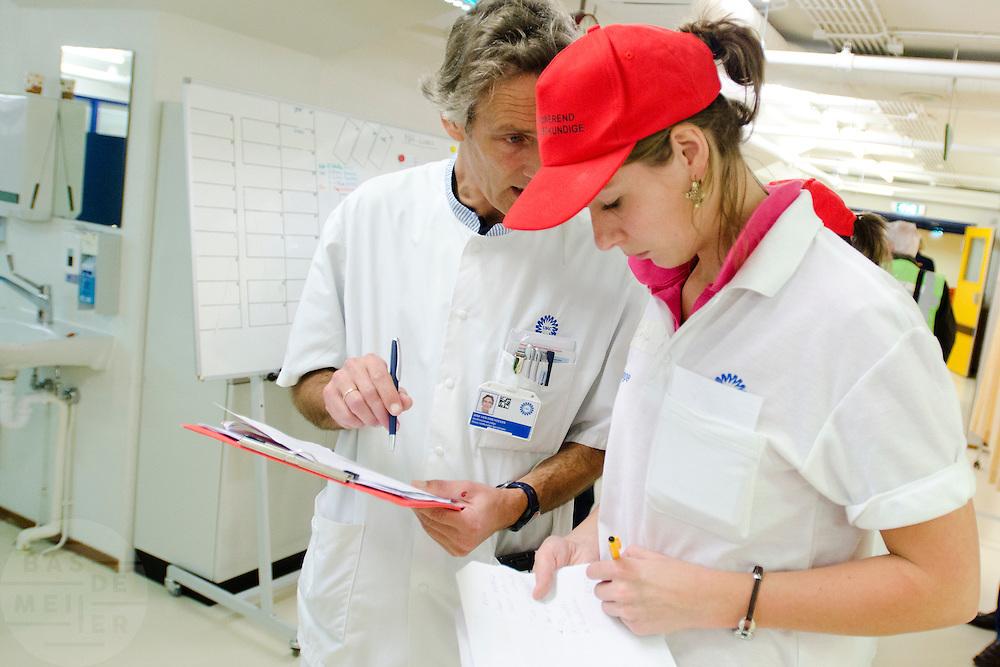 Verpleegkundigen overleggen met elkaar. In het Calamiteitenhospitaal in Utrecht wordt een rampenoefening gehouden. De nadruk ligt op de contaminatie, door een gekantelde vrachtwagen zijn veel slachtoffers in aanraking gekomen met een chemische stof. Voor het eerst wordt er geoefend met een zogenaamde decontaminatietent. Als de tent bevalt, schaft het ziekenhuis zo'n tent aan. Bij de 'ramp' zijn 100 slachtoffers gevallen.<br /> <br /> Nurses are in discussion. In the Trauma and Emergency Hospital in Utrecht an calamity training was held. The emphasis is on the contamination by an overturned truck, many victims are contaminated by a chemical. For the first time a so-called decontamination tent was used. If the tent fulfills the expectations, a tent will be purchased. The 'calamity' caused 100 victims.