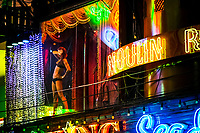 A pole dancer stands in a window of a go-go bar along Walking Street in Pattaya, Thailand.
