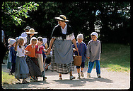 Schoolkids & women dressed as peasants walk along path @ Ecomusee folk museum; Ungersheim, Alsace. France