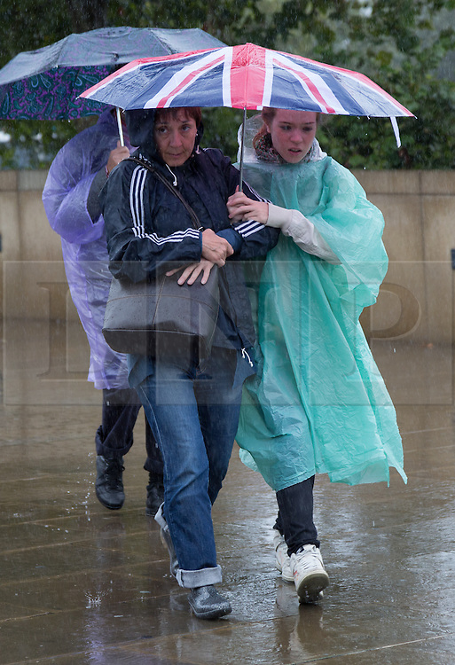 © Licensed to London News Pictures. 26/08/2014. London, UK. Tourists with umbrellas near the Tower of London. Heavy rain and cold weather are forecast for the rest of the day. Photo credit : Vickie Flores/LNP