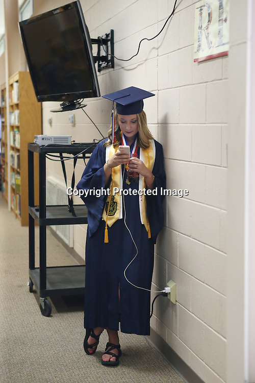 Lauren Wood | Buy at photos.djournal.com<br /> Katie Stevens checks her phone that is charging as she and other seniors wait in the library before the Baldwyn High School graduation ceremony Friday evening at the high school.
