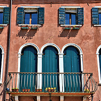 Residential Balcony in Sant'Elena in Venice, Italy<br /> The core of Venice is filled with tourist attractions which are, naturally, filled with crowds of tourists.  But stroll to the far eastern island of Sant'Elana if you want to experience how the local Venetians live. You'll see people bartering at street produce stands, chatting with their neighbors, washing the sides of their moored boats, hanging their laundry to dry and watering the flower pots on their small balconies.
