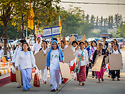 """02 JANUARY 2015 - KHLONG LUANG, PATHUM THANI, THAILAND: People walk into the grounds at Wat Phra Dhammakaya on their way to start the 4th annual Dhammachai Dhutanaga (a dhutanga is a """"wandering"""" and translated as pilgrimage). More than 1,100 monks are participating in a 450 kilometer (280 miles) long pilgrimage, which is going through six provinces in central Thailand. The purpose of the pilgrimage is to pay homage to the Buddha, preserve Buddhist culture, welcome the new year, and """"develop virtuous Buddhist youth leaders."""" Wat Phra Dhammakaya is the largest Buddhist temple in Thailand and the center of the Dhammakaya movement, a Buddhist sect founded in the 1970s.   PHOTO BY JACK KURTZ"""