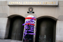"© Licensed to London News Pictures. 11/03/2019. London, UK. Lacey Rigby, an activist from anti-knife campaign ""Take a Knife, Save a Life"" ties purple ribbons around the Old Bailey in memory of 17-year-old Jodie Chesney who was stabbed to death in a playground in Harold Hill, Romford, on 1 March. Today, Manuel Petrovic appears in court charged with the murder of Jodie Chesney. Photo credit : Tom Nicholson/LNP"