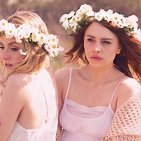 Two young women standing together in the sun wearing white summer dresses with head garlands made from white daisiy flowers