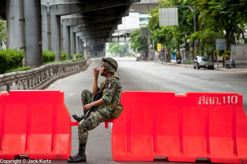 16 MAY 2010 - BANGKOK, THAILAND: Thai troops man a checkpoint near Sala Daeng Intersection in Bangkok. Movement beyond the barricade drew warning shots and ultimately live fire. Thai troops and anti government protesters clashed on Rama IV Road again Sunday afternoon in a series of running battles. Troops fired into the air and unidentified snipers shot at pedestrians on the sidewalks. At one point Sunday the government said it was going to impose a curfew only to rescind the announcement hours later. The situation in Bangkok continues to deteriorate as protests spread beyond the area of the Red Shirts stage at Ratchaprasong Intersection. Many protests now involve people who have not been active in the Red Shirt protests and live in the vicinity of Khlong Toei slum and Rama IV Road. Red Shirt leaders have called for a cease fire, but the government indicated that it is going to go ahead with operations to isolate the Red Shirt camp and clear the streets.      PHOTO BY JACK KURTZ
