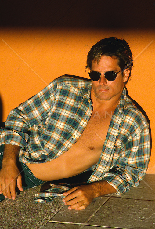 Man with an open shirt with sunglasses leaning against a wall at sunset