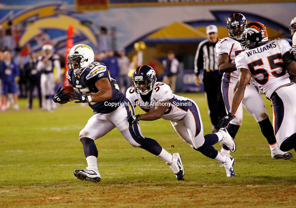 San Diego Chargers fullback Mike Tolbert (35) tries to avoid a diving tackle attempt by Denver Broncos running back Lance Ball (35) on a first quarter run inside the Broncos red zone during the NFL week 11 football game against the Denver Broncos on Monday, November 22, 2010 in San Diego, California. The Chargers won the game 35-14. (©Paul Anthony Spinelli)