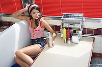 Young Woman Reclining in a Diner Booth