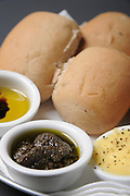 Freshly baked rolls with olive dip, garlic butter and olive oil with vinegar