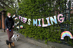"© Licensed to London News Pictures. 01/04/2020. London, UK. A woman wearing a face mask walks past a 'KEEP SMILING"" hand painted sign and colourful rainbows displayed outside a school in north London. Rainbows are used as a symbol of peace and hope. Photo credit: Dinendra Haria/LNP"