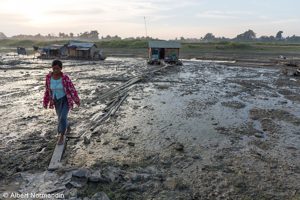 Woman on planks across mud from her home on river, Mandalay