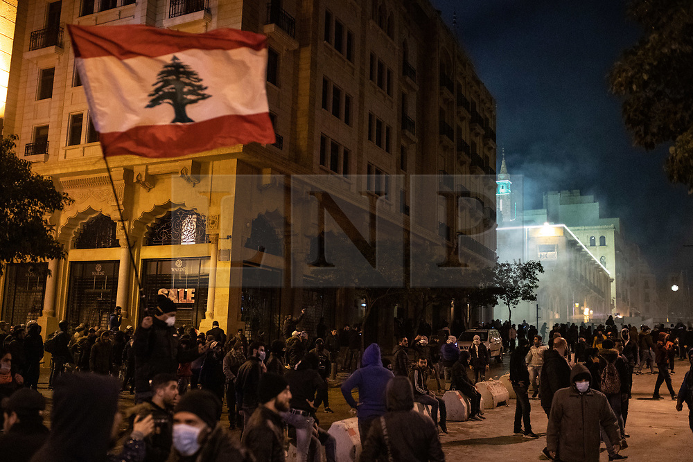 """© Licensed to London News Pictures. 22/01/2020. Beirut, Lebanon. Demonstrators riot outside government buildings on the streets of Beirut following the announcement late last night that a government has been formed. Police respond with tear gas and water cannon against the anti-government demonstrators. Violence has been escalating in the capital following a """"week of wrath"""", where demonstrators were campaigning against government corruption and economic crisis. Photo credit : Tom Nicholson/LNP"""