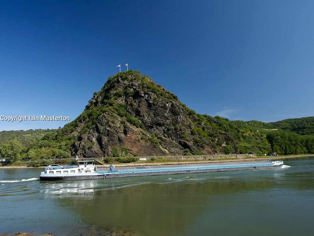Barge sailing past famous Loreley rock on the River Rhine in Germany
