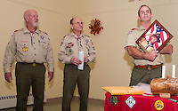Retiring  Boy Scout leaders Gary Doucette with 26 years and Carl Gebhardt with 43 years receive dedication plaques from Kurt Webber during Troop 243's meeting Wednesday evening at the Gilford Community Center.  (Karen Bobotas/for the Laconia Daily Sun)