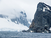 Peaks rise steeply from the Southern Ocean at Graham Land, in Antarctica.