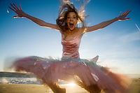 Happy girl jumps for joy at the beach, Los Angeles, California, USA, America, at dusk