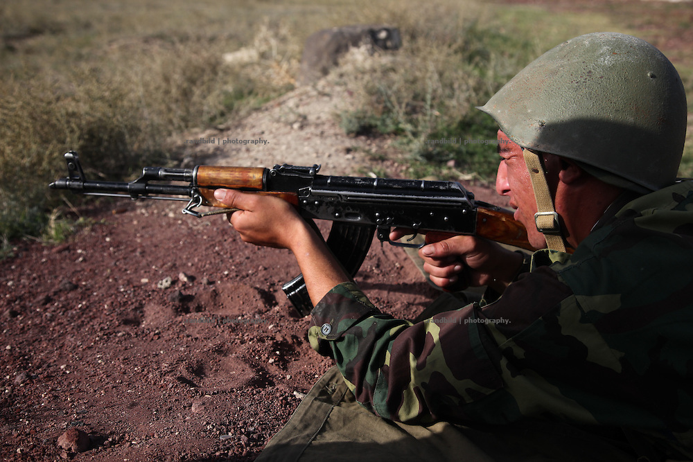 An armenian recruit getting a lesson in Kalashnikov shooting on an military exercise ground near armenian capital Yerevan.