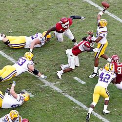 November 25, 2011; Baton Rouge, LA, USA; LSU Tigers quarterback Jordan Jefferson (9) is pressured by Arkansas Razorbacks defenders during the fourth quarter of a game at Tiger Stadium. LSU defeated Arkansas 41-17. Mandatory Credit: Derick E. Hingle-US PRESSWIRE