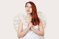 Young woman dressed as an angel looking away against gray background