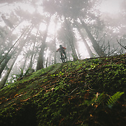 Owne Dudley rides a rock drop in the mist of the Northwest Rainforest near Bellingham, WA.