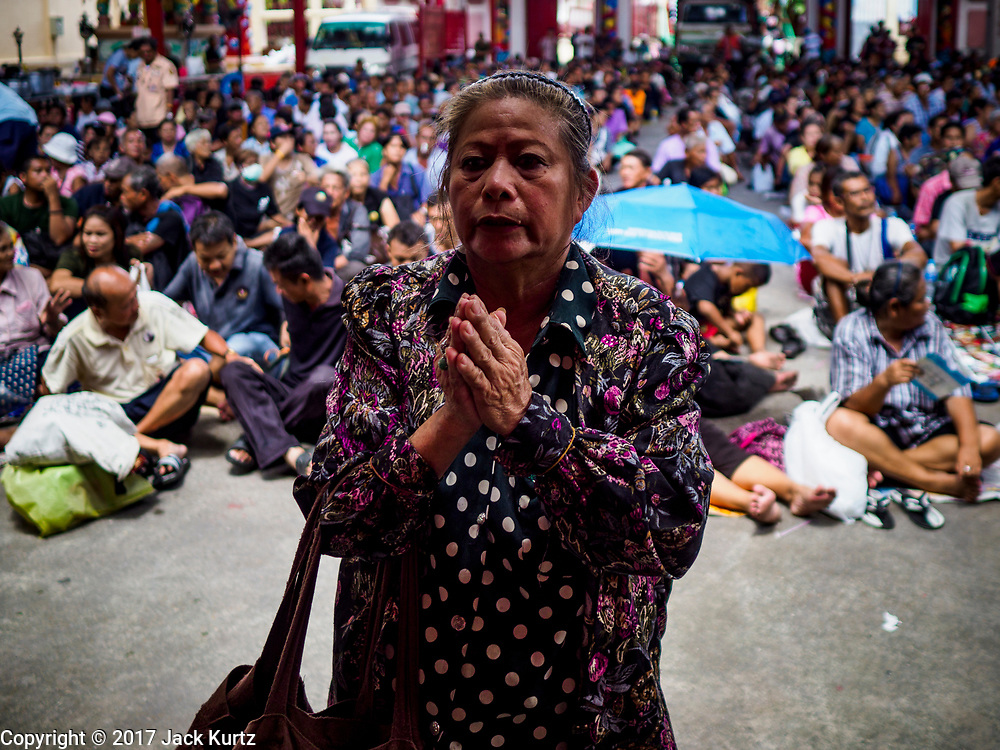 04 SEPTEMBER 2017 - BANGKOK, THAILAND: A woman prays at the entrance to Chaomae Thapthim Shrine while poor people from nearby communities wait for a food distribution to begin. About 1,000 people came to Chaomae Thapthim Shrine for the annual food distribution. Staples, like rice and cooking oil, are donated to the shrine throughout the year and donated to poor people from the communities around the shrine. Food distributions like this are a tradition at Chinese shrines in Bangkok and a common way of making merit for the people who donate the staples.     PHOTO BY JACK KURTZ