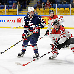 WHITBY, - Dec 18, 2015 -  Game #12 - Bronze Medal Game, Team Canada East vs. United States at the 2015 World Junior A Challenge at the Iroquois Park Recreation Complex, ON. William Knierem #24 of Team United States and Geoff Lawson #23 of Team Canada East follow the play during the first period.<br /> (Photo: Shawn Muir / OJHL Images)