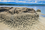 Weathered rock along the shore of the Strait of Georgia looking towrads Vancouver Island<br /> Hornby Island in the Gulf Islands<br /> British Columbia<br /> Canada