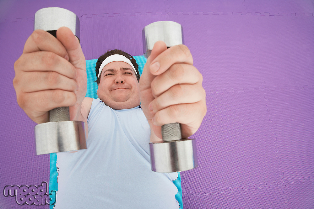 Overweight Man lying down Lifting dumbbells overhead view