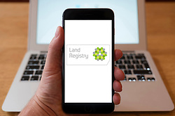 Using iPhone smartphone to display logo of The Land Registry, which registers ownership of land in England and Wales