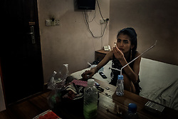 A prostitute is smoking Ice in a hotelroom in Phnom Penh, Cambodia.<br />