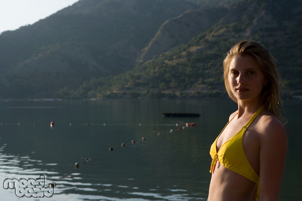 Blonde woman in bikini looks back at camera in morning sunlight of lake