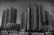 Skeletal frames of a high-rise complex in the northern section of Xingtai in 2015 there are huge complexes, standing unfinished or sparsely occupied.  These unfinished towers lack the frenetic construction crews working day and night the world has become accustomed to in China.  Instead, there are small construction crews working in a limited areas two of the six towers while four will stand idlely as empty shells.  This would have been a strange sight in this country that has enjoyed double digit-growth for three decades.  Xingtai, Hebei Province, China.