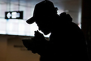 A homeless man, in silhouette, eats soup provided by Volunteers from Groupo Esperanca a Brazilian and Nikkei Japanese catholic charity group at Hamamatsu station. Hamamatsu, Shizuoka, Japan. Saturday, March 21st 2009. Despite many Brazilian immigrants in Japan suffering badly in the economic crisis of 2008 and 2009, such charity groups provided food clothes and company to homeless immigrants and native japanese in Hamamatsu and other cities across Japan.