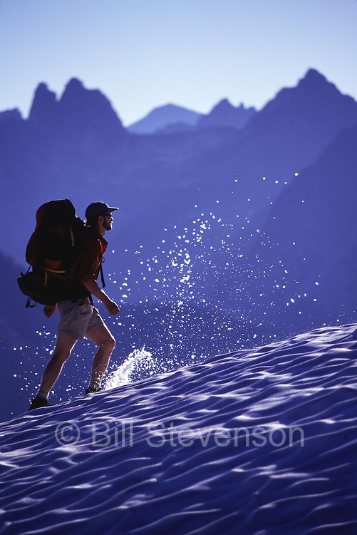 A photo of a man hiking in the snow during summer near Maple Pass, WA.