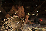 Huaorani Indian - Gewe Kaiga making a basket from local forest materials. Gabaro Community. Yasuni National Park.<br /> Amazon rainforest, ECUADOR.  South America<br /> This Indian tribe were basically uncontacted until 1956 when missionaries from the Summer Institute of Linguistics made contact with them. However there are still some groups from the tribe that remain uncontacted.  They are known as the Tagaeri. Traditionally these Indians were very hostile and killed many people who tried to enter into their territory. Their territory is in the Yasuni National Park which is now also being exploited for oil.