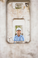 Portrait of male architect through pillars at construction site